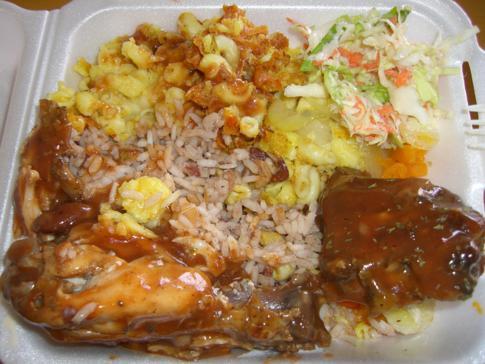 Klassischer Lunch in Grenada, bestehend auf Hühnchen, Reis, Macaroni Pie, Salat und Provision