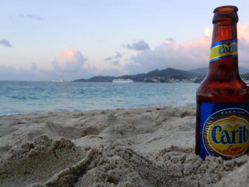 Ein Carib beim Sonnenuntergang am Grand Anse Beach