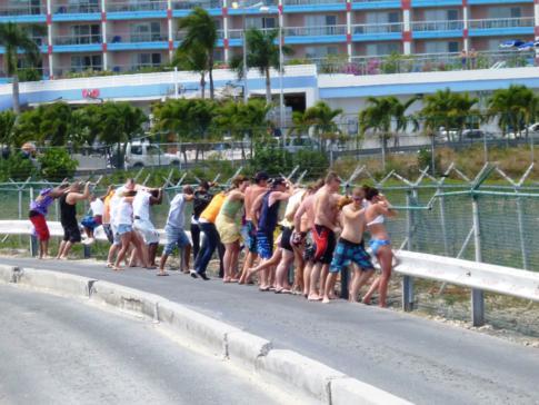 Zaunsurfing am Maho Beach - die startenden Flugzeuge blasen ordentlich Triebwerksluft in die waghalsigen Menschen